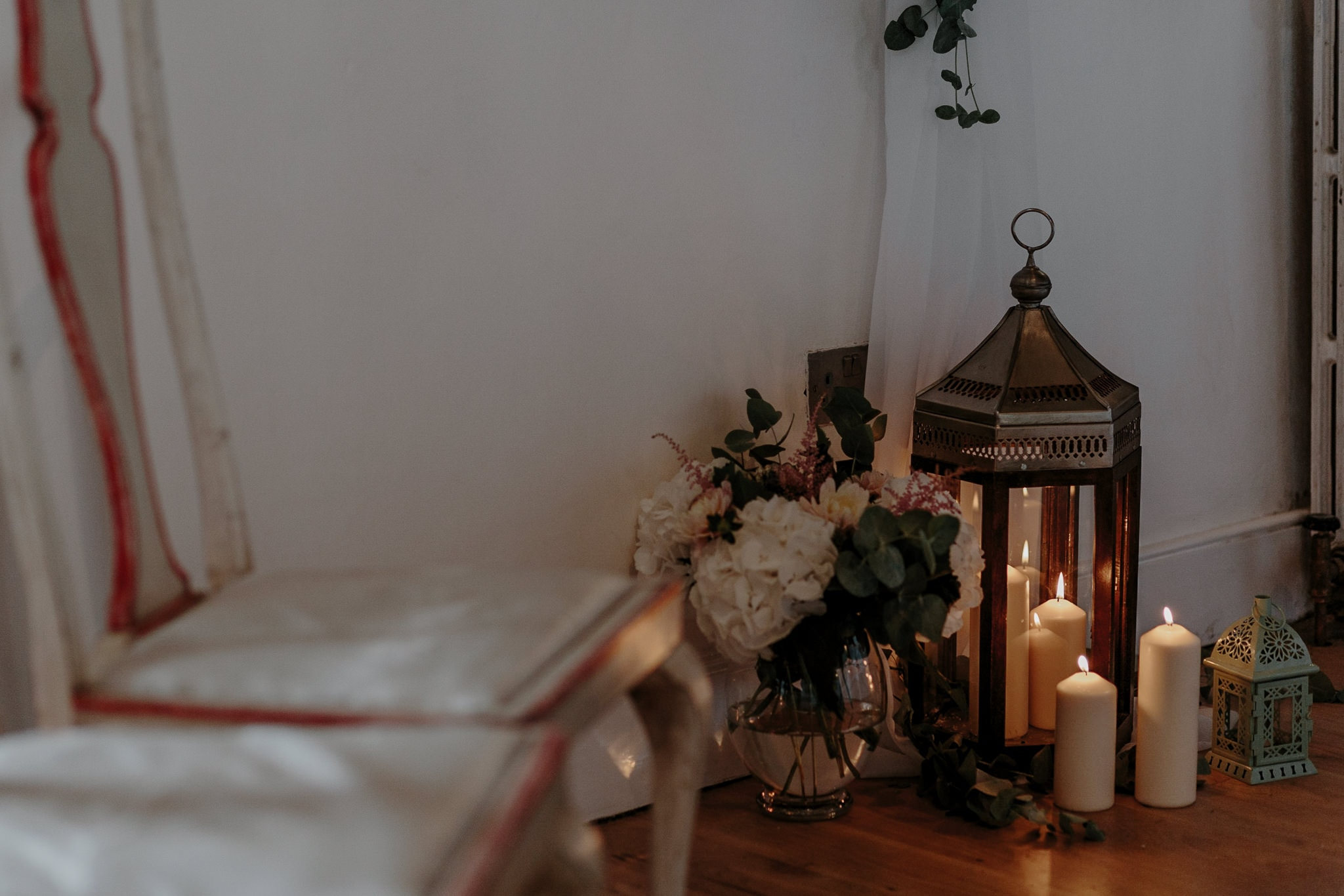candles in lanterns accompanied by floral decoration in the ceremony room at Carreglwyd Estate