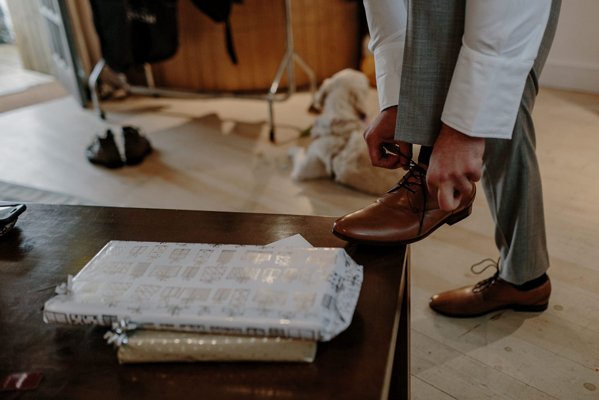 groom tying his shoe laces during morning wedding preparations