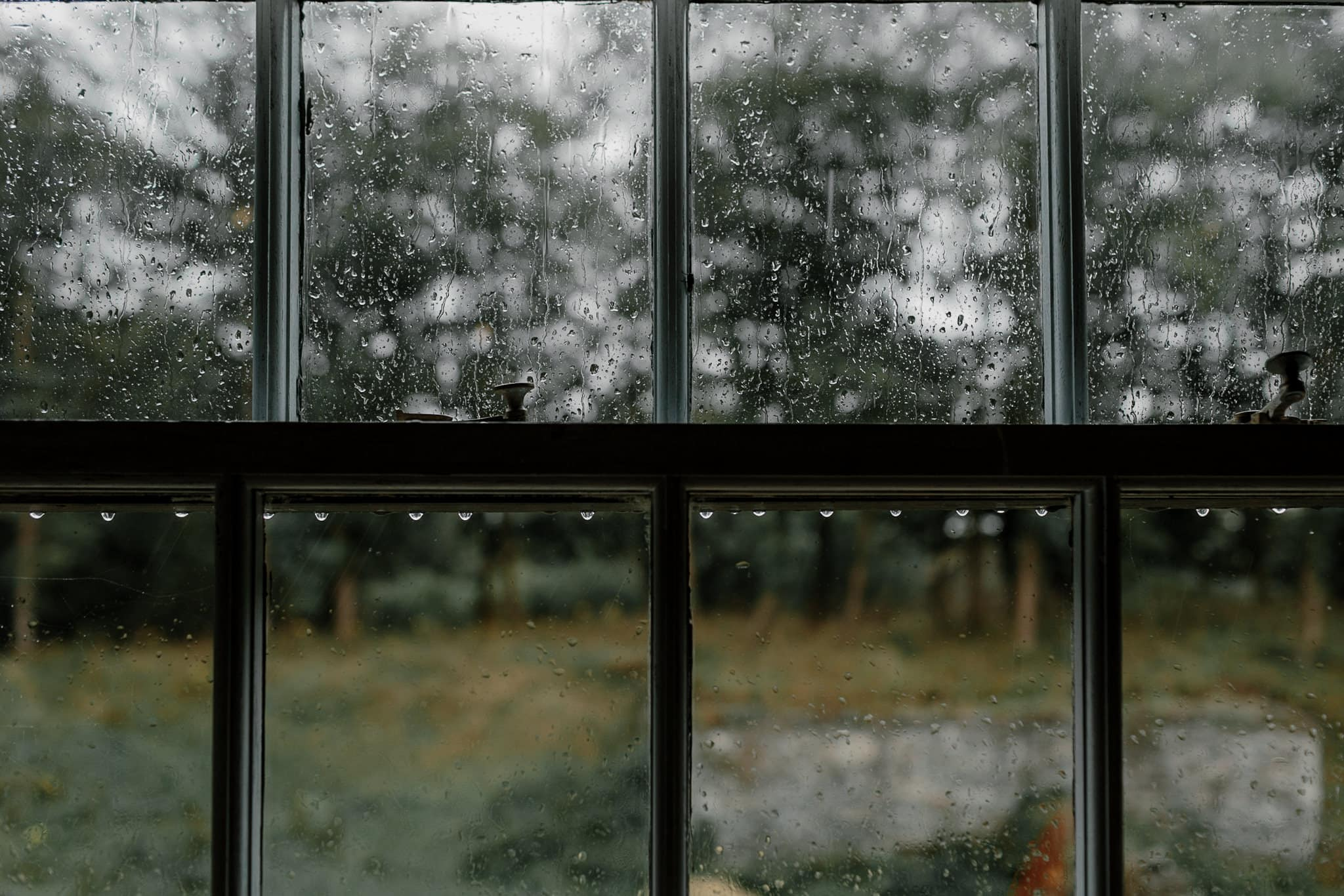 A close-up of a windo pane showing rain drops at Carreglwyd Estate