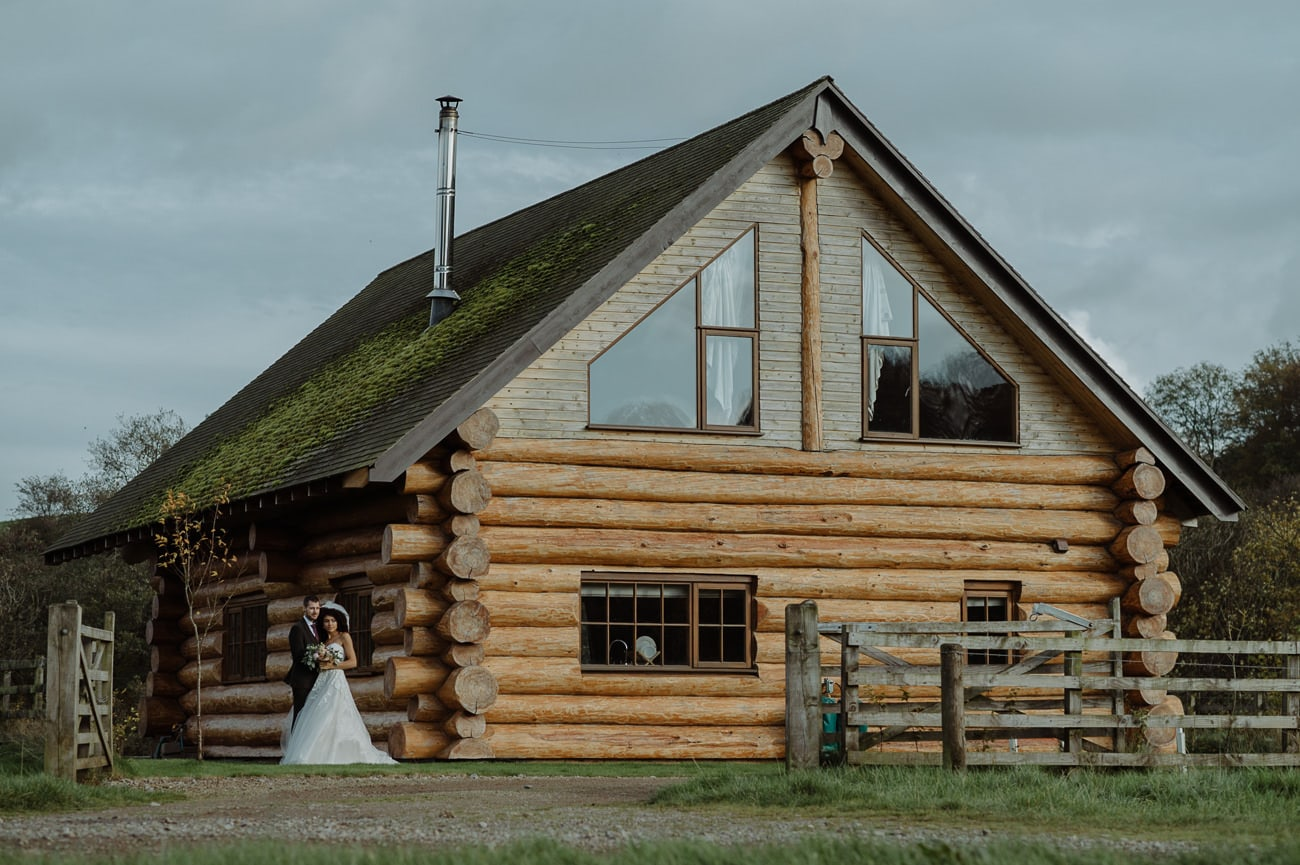 Married Couple Standing In Front of Barn at Hidden River Cabins